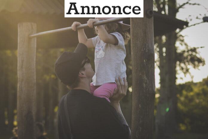 Mand hjælper en lille pige op på en monkey bar